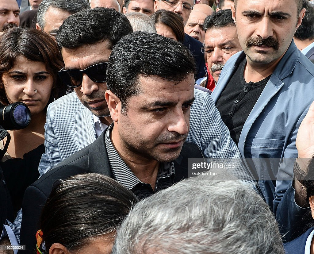 Selahattin Demirtas, (center) co-leader of the pro Kurdish Democratic Party of Peoples (HDP) walks through the crowd on October 11, 2015 in Ankara, Turkey. Scuffles broke out as police prevented pro-Kurdish politicians and other mourners from laying carnations at the site of two suspected suicide bombings that killed 95 people and wounded hundreds in Turkey's deadliest attack in years. Police insisted investigators were still working at the site. Turkish PM Davutoglu declares three days of national mourning over Ankara bomb attacks.