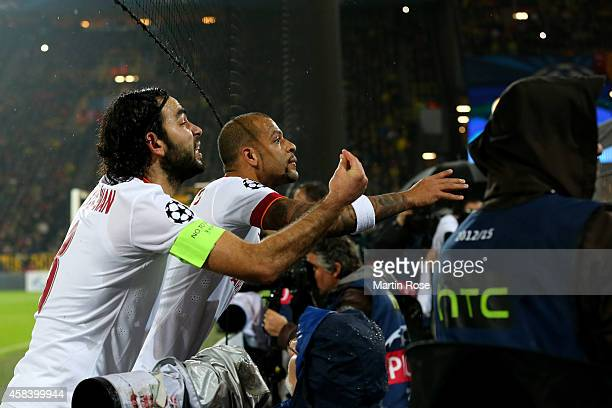 Selcuk Inan of Galatasaray and Felipe Melo of Galatasaray plead with their fans after fireworks are thrown onto the pitch during the UEFA Champions...