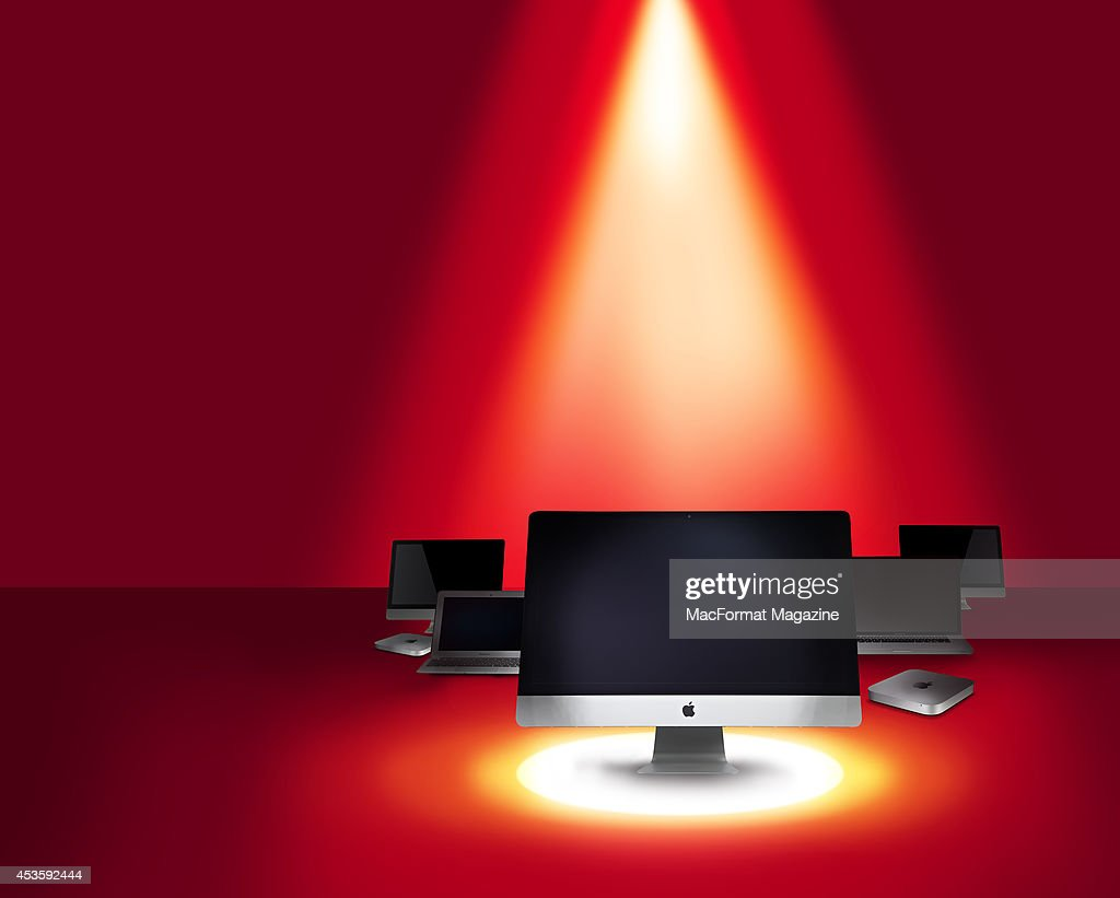 A selection of Apple computers, including iMac, Mac Mini and MacBook models, photographed on a red background beneath a spotlight for a feature on buying an Apple computer in 2014, taken on October 4, 2013.