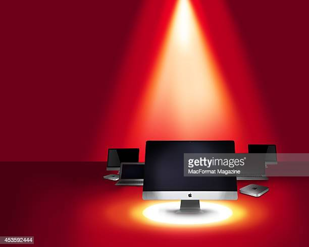 A selection of Apple computers including iMac Mac Mini and MacBook models photographed on a red background beneath a spotlight for a feature on...