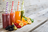 Selection of colorful smoothies, rustic wood background, copy space