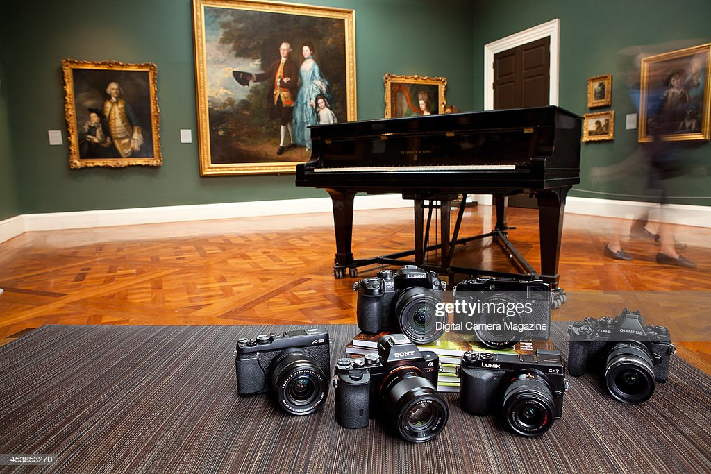 A selection of compact system cameras photographed in an art gallery, including Fujifilm, Olympus, Panasonic and Sony models, taken on January 29, 2014.