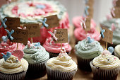 A selection of pink, blue, cream cupcakes on a table for a baby shower with a big cake in the background.