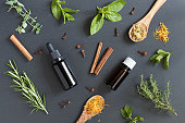 Two bottles of essential oil with a selection of herbs on a dark background - peppermint, basil, thyme, rosemary, cinnamon, clove, oregano, chamomile, calendula