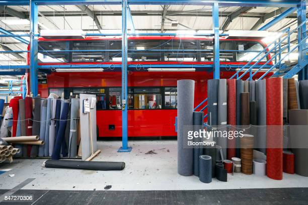 A selection of flooring and seating materials stand next to an Enviro 400 London bus at the Alexander Dennis Ltd factory in Scarborough UK on...
