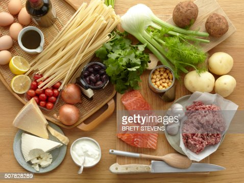 Selection of fresh raw foods with eggs, pasta, herbs, cheese, vegetables, salmon and minced pork