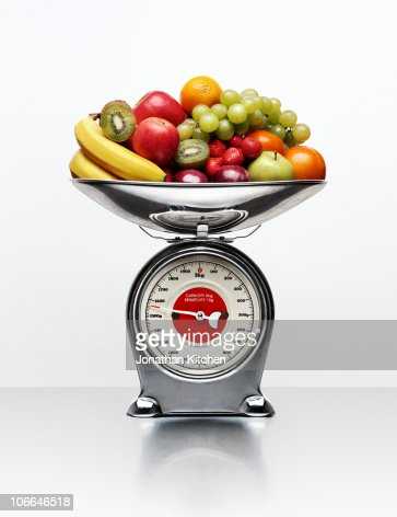 A selection of fruit on a weighing scale : Stock Photo