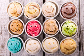 Selection of gourmet flavours of Italian ice cream in vibrant colors served on an old rustic wooden table in an ice cream parlor, overhead view