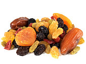 a DSLR royalty free digital image of a mixed selection of juicy looking dried fruits, including raisins, sultanas, dates, currants, apricots, isolated against a plain white background
