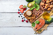 Selection of healthy food for heart, salmon fish avocado olive oil pumpkin seeds nuts broccoli green spinach berries on a white rustic wooden table. Copy space background, top view