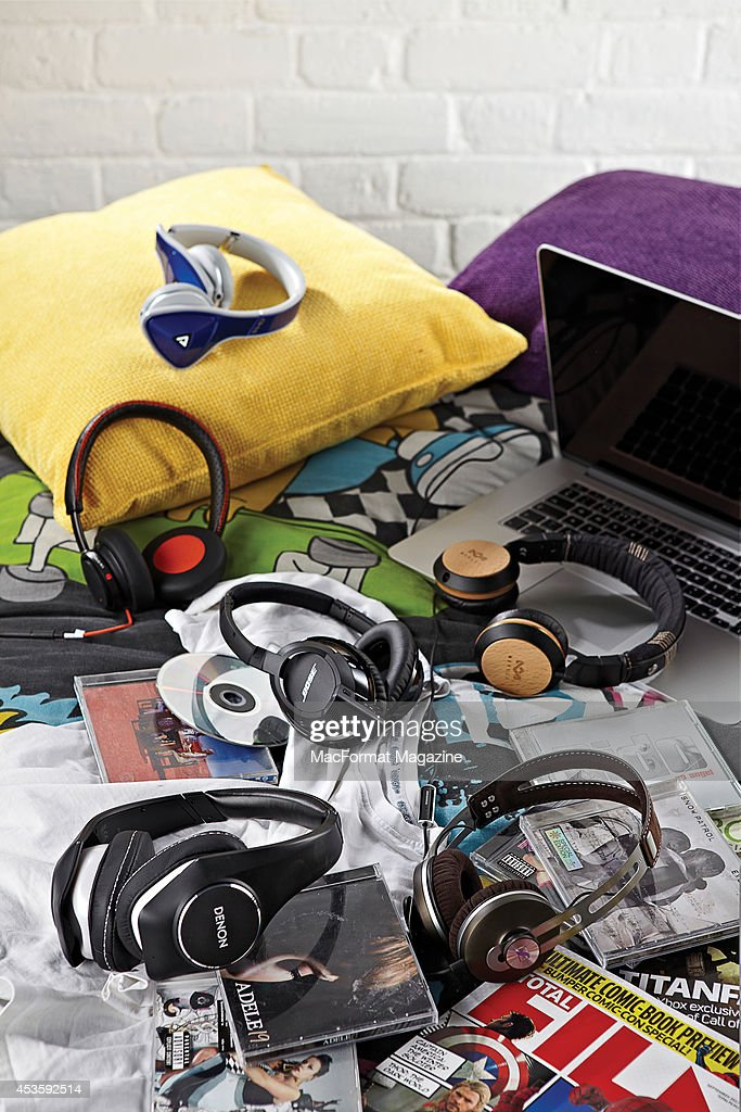 A selection of high-end headphones photographed in a domestic setting, with CD cases and an Apple MacBook, taken on November 1, 2013.