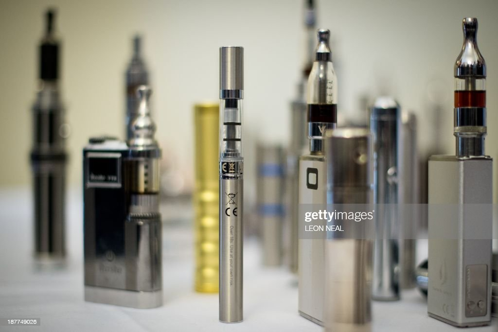 A selection of 'Nicotine Containing Products', or 'NCP's are displayed during 'The E-Cigarette Summit' at the Royal Academy in central London on November 12, 2013. The merits of e-cigarettes were thrashed out at a one-day gathering of scientists, experts, policymakers and industry figures at the Royal Society in London. The use of electronic cigarettes -- pen-sized battery-powered devices that simulate smoking by heating and vaporising a liquid solution containing nicotine -- has grown rapidly. AFP PHOTO / LEON NEAL