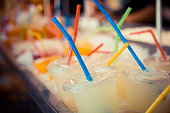 Selection of plastic cups with grapefruit juice and colored straws, in red, yellow, blue and green. Close up and Focus Selective