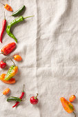 Selection of summer chilli peppers on an ivory linen surface
