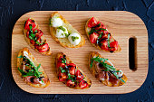 Selection of tasty Italian bruschetta on toasted baguette topped with tomatoes, Prosciutto di Parma, Mozzarella balls with pesto sauce, arugula and balsamic glasse sauce on cutting board. Top view.