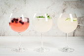 Selection of three kinds of gin tonic: with blackberries, with lime, with mint leaves. In glasses on a white background. Copy space