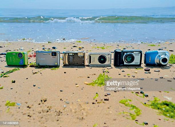 A selection of underwater compact digital cameras lined up on a beach taken on May 20 2007