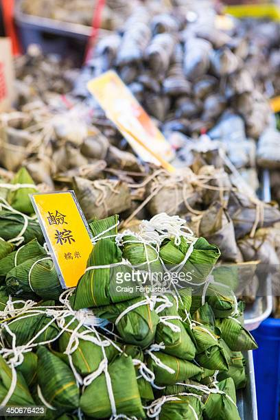 A selection of zongzi arranged for sale in a market