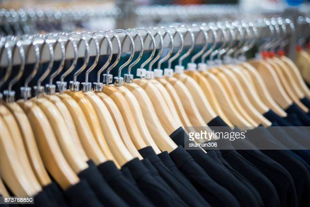selective focus hand holding color Dress cloth and Shirts hanging stack