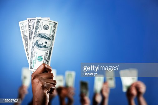 Hand holds up spotlit bundle of dollars; more in background