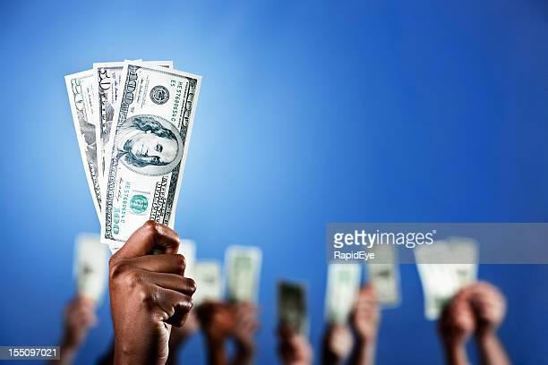 Geringe Tiefenschärfe, viele Fäuste halten Geld