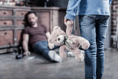 My toy. Selective focus of a fluffy bear being held by a nice sad depressed girl while looking at her father