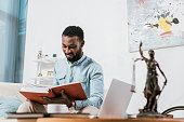 selective focus of african american man reading book in living room
