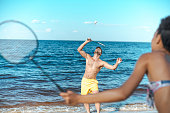 selective focus of multicultural couple playing badminton on sandy beach