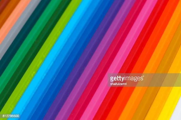 Selective focus of pencil colours on near-white chopping board