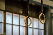 Selective focus of wooden gymnastic rings in front of a large window. Horizontal composition.
