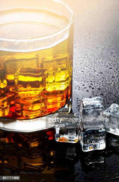 selective focus pure whisky with ice cube inside whisky glass on wet background