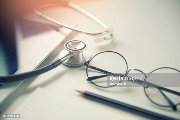 Selective focus side view of stethoscope on working space with tablet and notebook for  patient consult