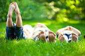Group of happy children lying on green grass outdoors in spring park.