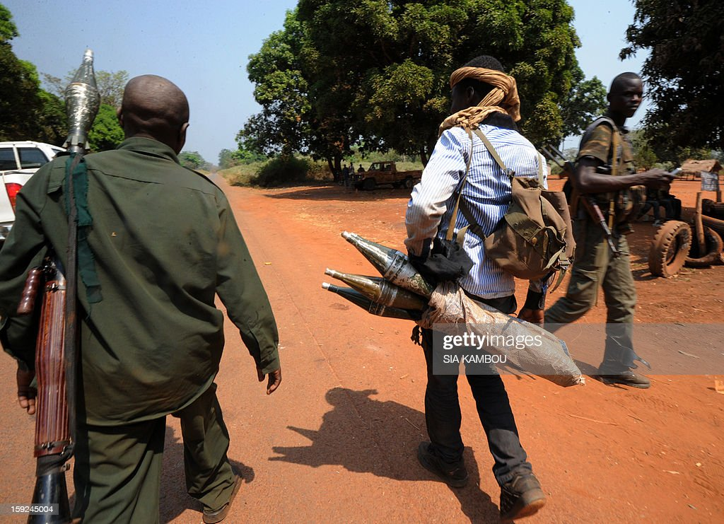 Seleka rebel coalition members, which launched a major offensive last month, carry weapons on January 10, 2013 in a village 12 kilometers from Damara, where troops of the regional African force FOMAC are stationned. Three-way peace talks between the Central African government, the rebel coalition that conquered much of the country over the past month and the political opposition began on January 9 in Gabon. With a lightning advance starting December 10, the rebels took over most of the Central African Republic. They are demanding that Central African President Francois Bozize step down, but the head of state, who took power in a 2003 coup, warned on the eve of the talks that he would not leave his job. AFP PHOTO/ SIA KAMBOU