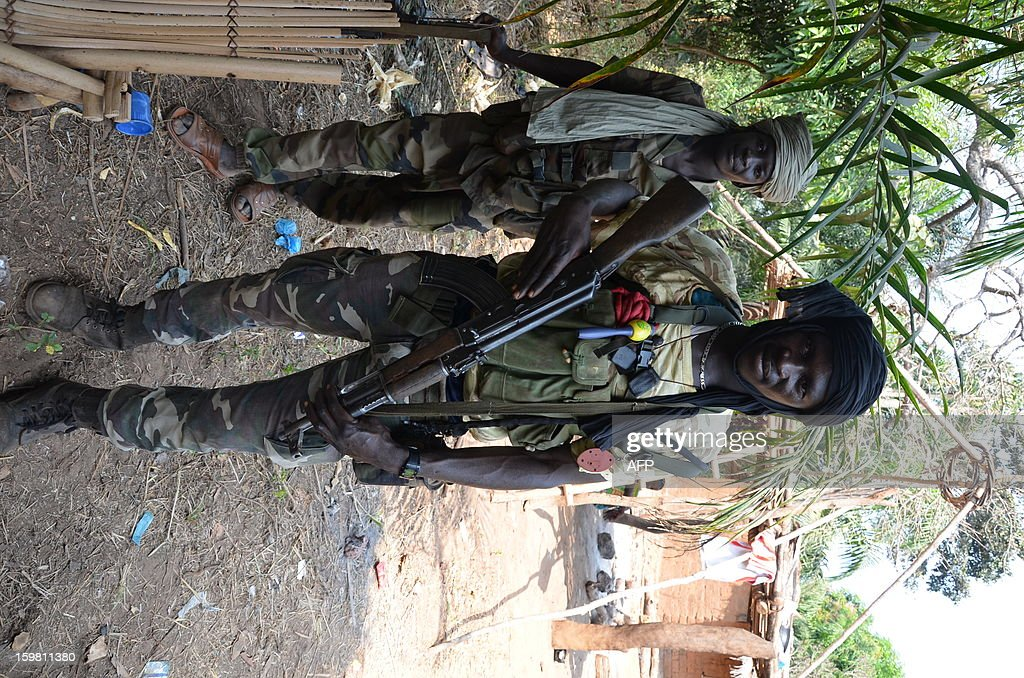 A Seleka rebel, wearing a jumping rope around his neck as a gris-gris, stands on January 17, 2013 north of Damara, 75 kms from the capital Bangui. Opposition lawyer Nicolas Tiangaye was on January 17 officially appointed prime minister of the Central African Republic's new national unity government, President Francois Bozize said after a ceremony in the capital Bangui. The announcement came in line with a peace deal struck between the ruling party, the Seleka rebels and opposition on January 13.