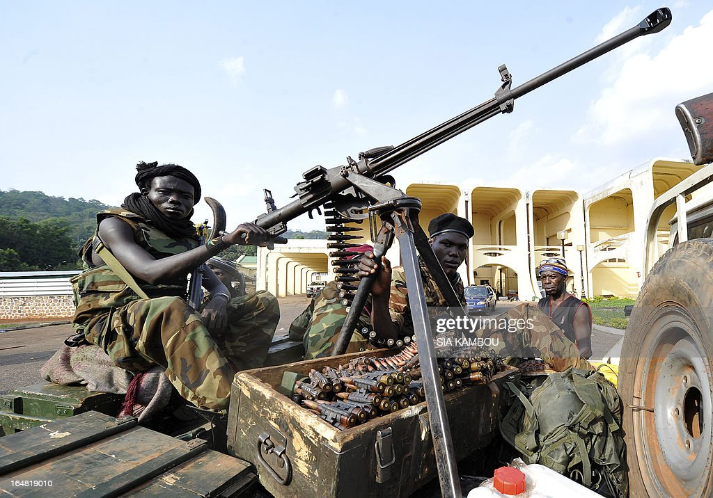 Seleka rebels sitting on a pick up truck mounted with a machine gun stand attention outside the pillaged presidential palace of deposed president in Bangui on March 28, 2013. Ousted Central African Republic president Francois Bozize, who fled after rebels took the capital Bangui, has taken refuge in Cameroon.