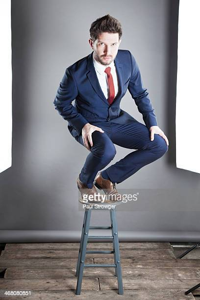Self, blue suit on stool.