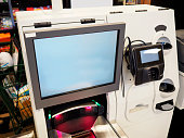 A self-service checkout till, also known in the industry as a Semi Attended Customer Activated Terminal (SACAT)) machine in a grocery store or supermarket.