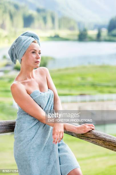 self confident woman is enjoying her day spa in a wellness resort while she is leaning on a wooden handrail