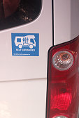 A blue self contained sticker on a campervan to illustrate a toilet is on board when in New Zealand.