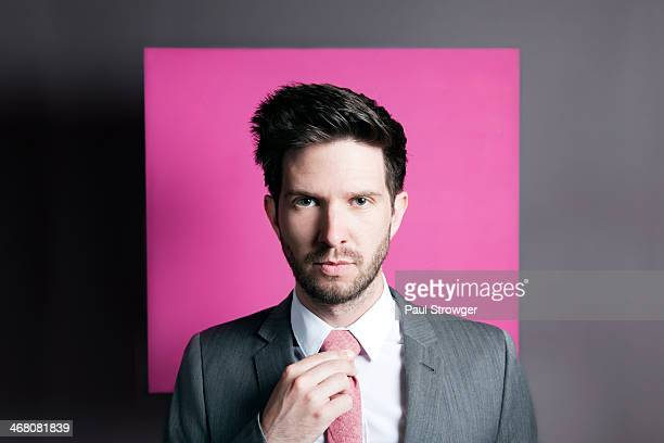Self, grey suit, pink tie and background.