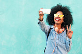Self portrait of beautiful young afro american woman making peace sign. Selfie Concept.