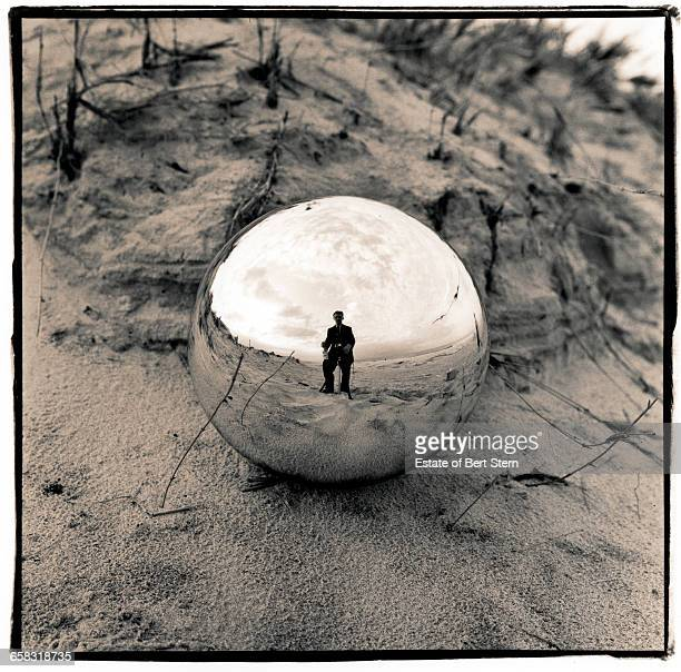 A self portrait of photographer Bert Stern reflected in a silvered glass bulb on the desert sands of New Mexico USA 1953 This was a Test shot for a...