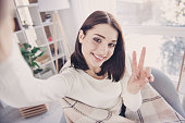 Self portrait of pretty, charming, nice, cute, stylish, brunette girl in pullover with modern hairstyle, shooting selfie gesturing v-sign to the front camera, wrapped in plaid, sitting in living room