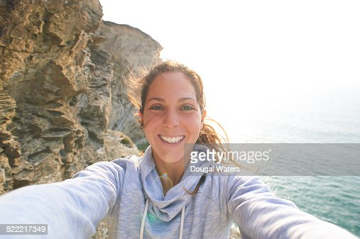 Self portrait of woman on rocky coastline.