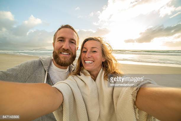 Self portrait of young couple on beach at sunset