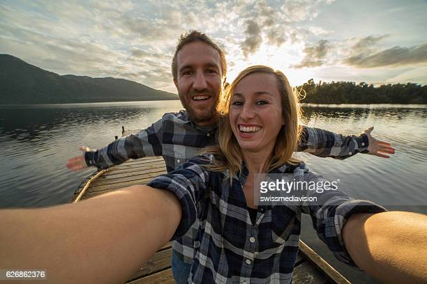 Self portrait of young couple on lake pier