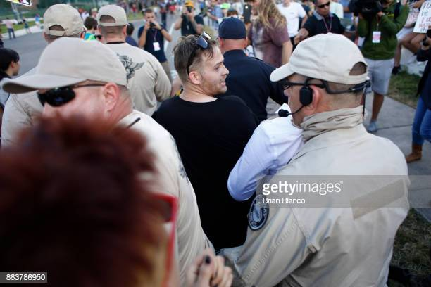 Selfdescribed white nationalist Colton Fears of Pasadena Texas center walks inside a group of Florida Highway Patrol troopers as the troopers assist...