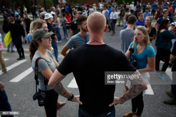 Selfdescribed white nationalist Tyler Tenbrink of Houston Texas watches as demonstrators gather near the site of a planned speech by Richard Spencer...