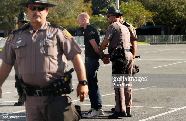 Selfdescribed white nationalist Tyler Tenbrink of Houston Texas is handcuffed by Florida Highway Patrol troopers as the troopers assist his safe...